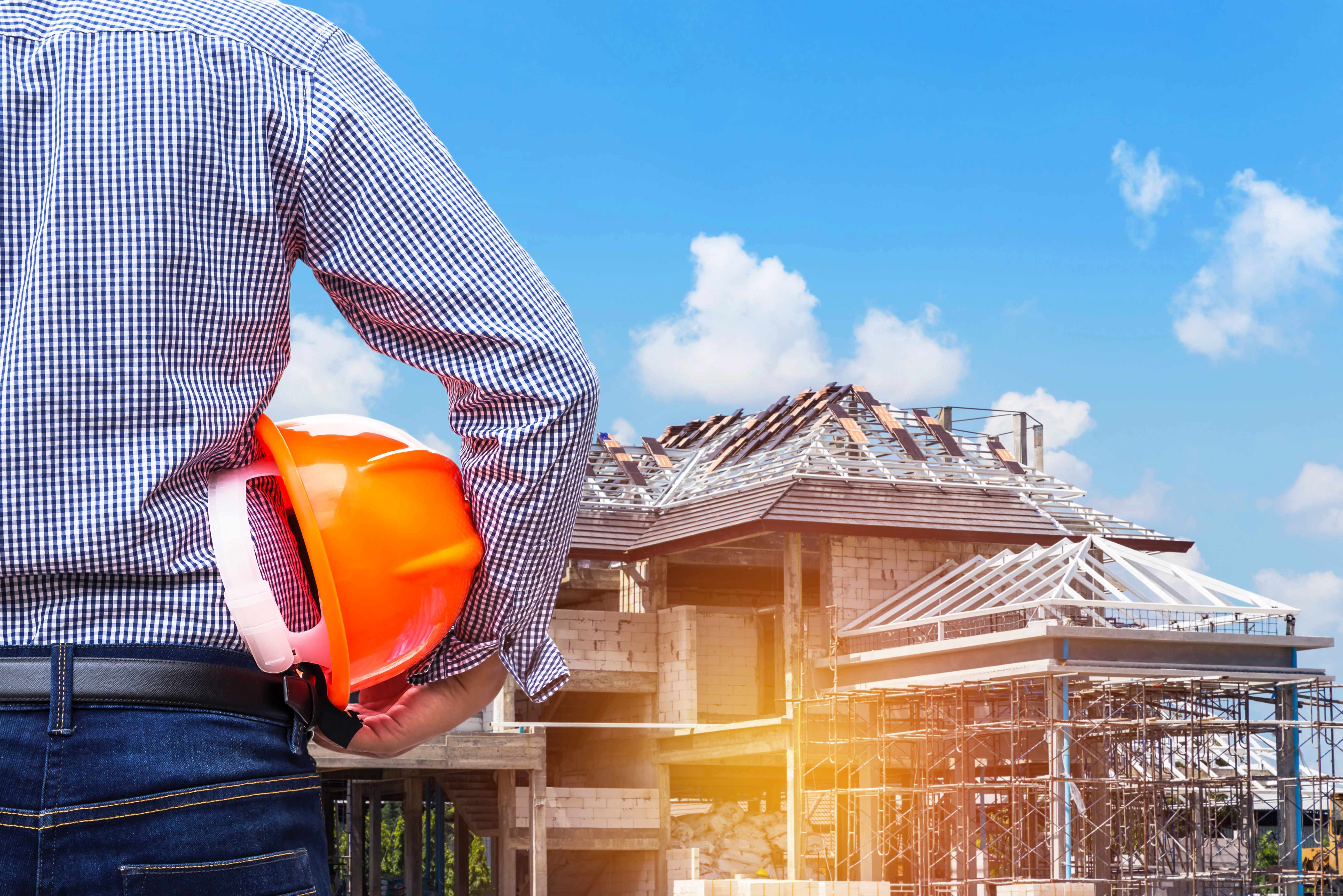 engineer-holding-safety-hat-at-new-home-construction