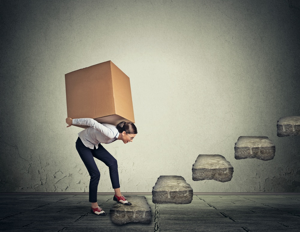 woman-carrying-large-heavy-box-on-her-back-upstairs